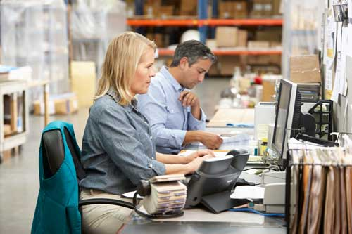 business-colleagues-working-at-desk-in-warehouse-PP3JZHS